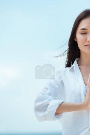 Photo pour Vue partielle de la femme asiatique avec des yeux fermés, faisant des gestes de mudra (sceau de la formule de politesse) namaste contre le ciel bleu - image libre de droit