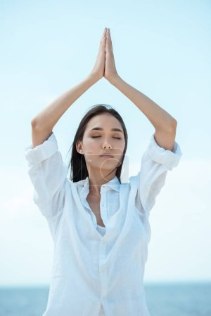 young asian woman with closed eyes standing in asana vrikshasana (tree pose) by sea