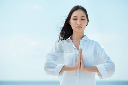 concentrated asian woman with closed eyes doing namaste mudra gesture in front of sea
