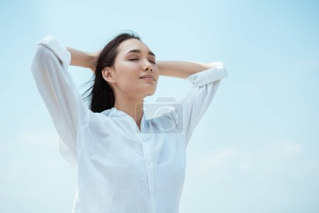 low angle view of young asian woman with closed eyes against blue sky