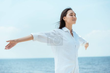 young asian woman with closed eyes standing with arms outstretched by sea