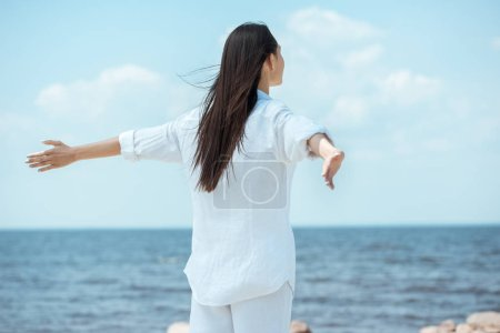 Photo for Rear view of woman standing with arms outstretched by sea - Royalty Free Image