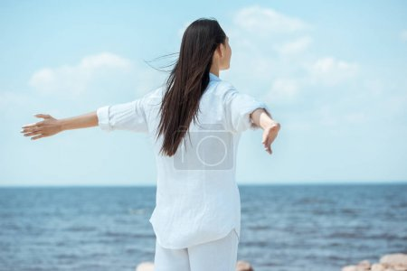 rear view of woman standing with arms outstretched by sea