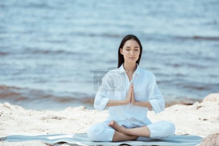 Photo for Attractive asian woman meditating in anjali mudra (salutation seal) pose on yoga mat by sea - Royalty Free Image