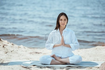 young asian woman in anjali mudra (salutation seal) pose on yoga mat by sea