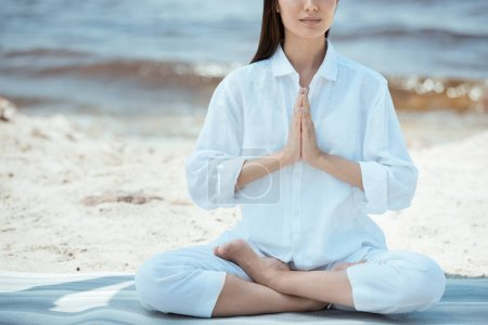 cropped image of woman meditating in anjali mudra (salutation seal) pose on yoga mat by sea