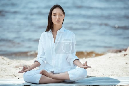 focused woman meditating in ardha padmasana (half lotus pose) on yoga mat by sea