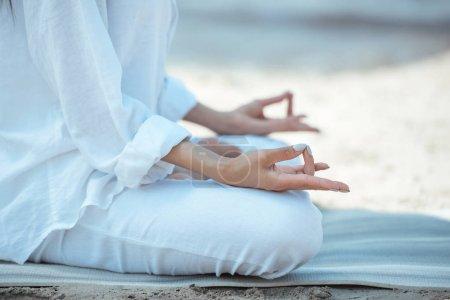 Photo pour Image recadrée de femme en ardha padmasana (demi lotus pose) sur des tapis d'yoga par la mer - image libre de droit