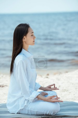Photo for Side view of young asian woman in ardha padmasana (half lotus pose) on yoga mat by sea - Royalty Free Image