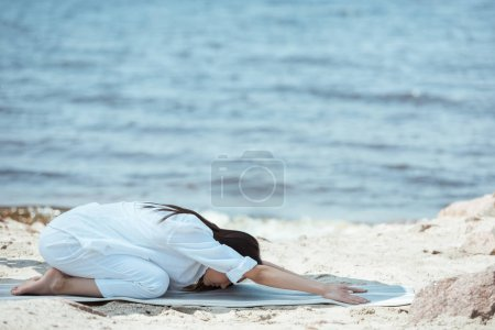 young woman practicing in balasana (child pose) pose on yoga mat in front of sea