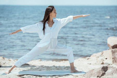 concentrated young asian woman practicing yoga in virabhadrasana (warrior II pose) on mat in front of sea