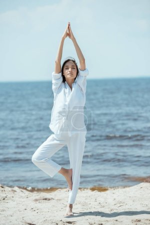 Photo for Young woman standing in asana vrikshasana (tree pose) on beach by sea - Royalty Free Image