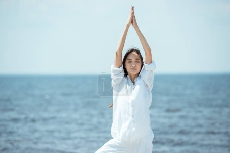 asian woman with closed eyes standing in asana vrikshasana (tree pose) on beach by sea