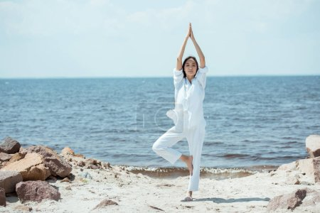 front view of asian woman standing in asana vrikshasana (tree pose) on beach by sea