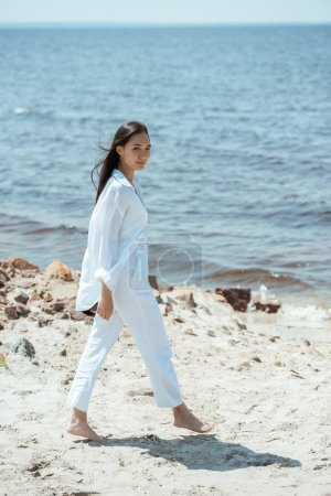 attractive young asian woman walking on beach by sea