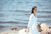 happy young asian woman looking at camera while standing on beach by sea