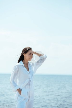 asian young woman with hand in pocket looking away in front of sea
