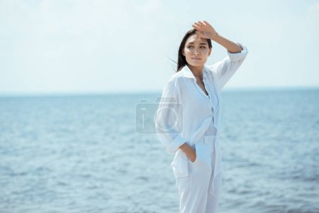 attractive asian woman with hand in pocket looking away in front of sea