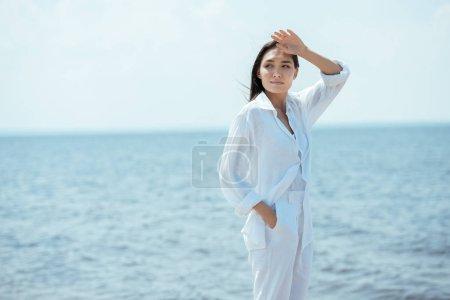 jolie femme asiatique, main dans la poche à la recherche de suite face mer