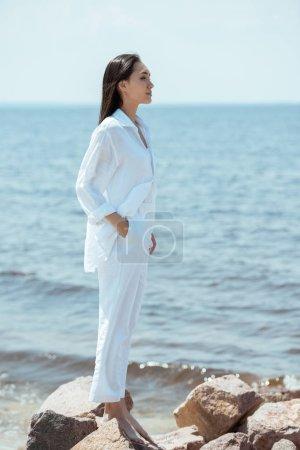 Photo pour Vue de côté de jolie femme asiatique avec main dans la position de la poche sur la plage au bord de mer - image libre de droit