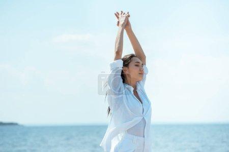 jolie femme asiatique avec des yeux fermés debout avec les bras larges en face de la mer