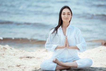 Photo for Attractive young asian woman in anjali mudra (salutation seal) pose on beach - Royalty Free Image