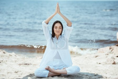 focused asian young woman meditating in lotus position and doing namaste mudra gesture above head by sea