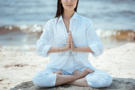 Photo for Cropped image of woman in anjali mudra (salutation seal) pose on beach by sea - Royalty Free Image