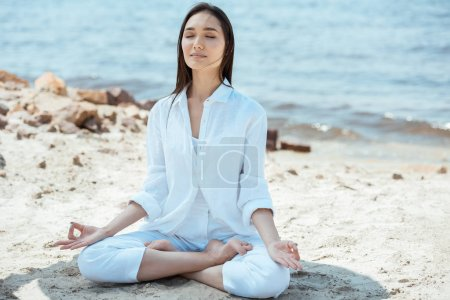 Photo for Asian woman with closed eyes meditating with akash mudra gesture in lotus position on beach - Royalty Free Image