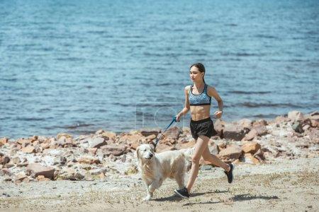 young asian sportswoman running with golden retriever on beach