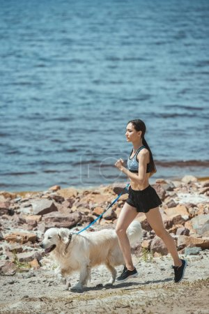 young asian female jogger running with golden retriever on beach