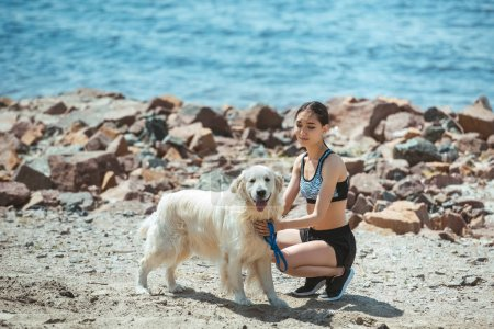 young asian woman embracing dog on beach in front of sea