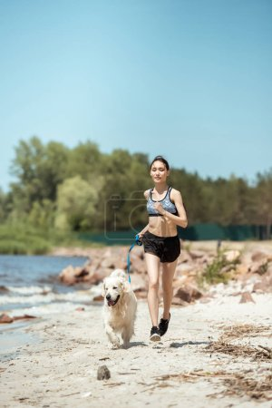 female athlete jogging with dog on beach during daytime