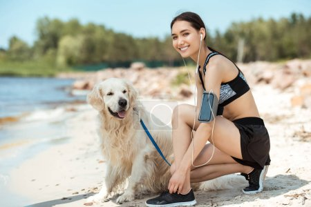 smiling asian sportswoman in earphones with smartphone in running armband case tying shoelaces near golden retriever on beach