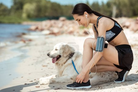 side view of asian sportswoman in earphones with smartphone in running armband case tying shoelaces near golden retriever on beach
