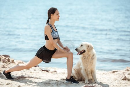 side view of asian female athlete doing lunges near golden retriever on beach