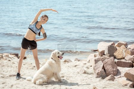 smiling asian sportswoman with smartphone in running armband case doing exercise while her golden retriever sitting near on beach