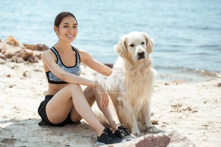 happy asian woman sitting with golden retriever on beach