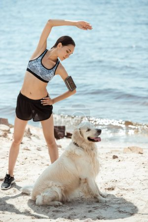 asian sportswoman with smartphone in running armband case doing exercise while her dog sitting near on beach