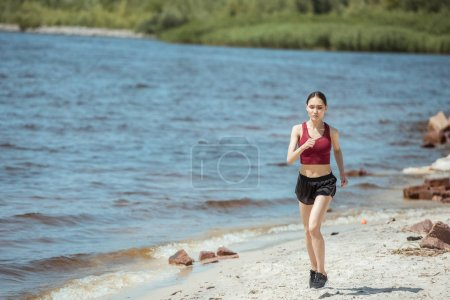 front view of young asian female jogger running on beach