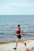attractive young asian female jogger running on beach