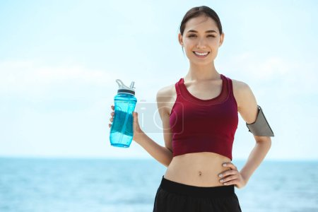Photo for Happy asian sportswoman with smartphone in running armband case holding bottle of water - Royalty Free Image