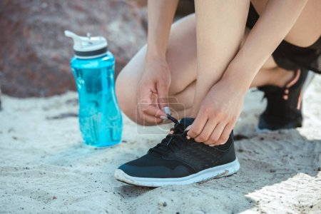 Photo for Cropped image of female athlete tying shoelaces near sport bottle with water - Royalty Free Image