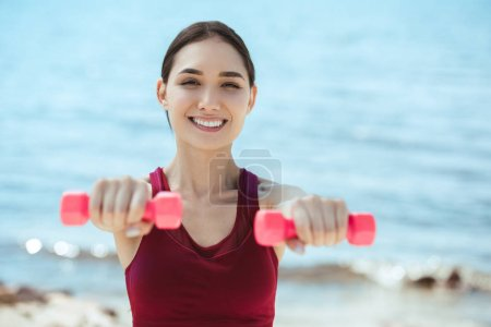 smiling asian sportswoman exercising with dumbbells in front of sea