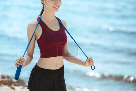 cropped image of smiling sportswoman holding jump rope on beach