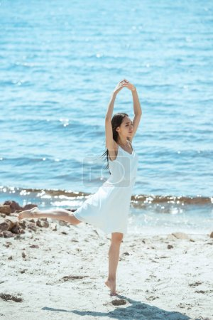 young asian woman in white dress dancing on beach by sea