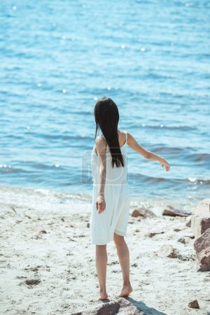 rear view of woman in white dress dancing on beach by sea