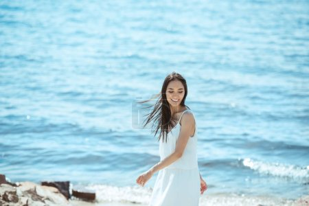 Photo for Smiling asian woman in white dress standing by sea during daytime - Royalty Free Image