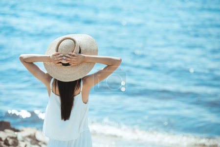 Photo for Rear view of woman in white dress and straw hat standing in front of sea - Royalty Free Image