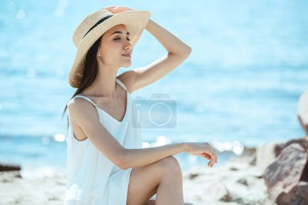 Photo for Smiling asian woman in straw hat and white dress by sea - Royalty Free Image